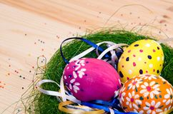 Easter eggs painted in a nest of grass with a bow. On wooden background Royalty Free Stock Image