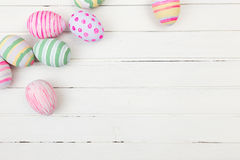 Easter eggs painted in pastel colors on a white. Wood background stock image