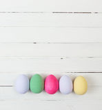 Easter eggs painted in pastel colors on white wood Stock Image
