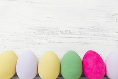 Easter eggs painted in pastel colors on white wood Stock Photo