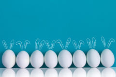 Easter eggs painted with rabbits ears and ballooons on the blue background. Easter eggs painted with rabbits ears and ballooons standing on the table on the blue stock photo