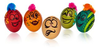 Easter eggs, painted in smiling and terrified cartoon faces look. Easter eggs, painted in smiling and terrified cartoon faces. Decorated eggs with funny colorful Stock Photography