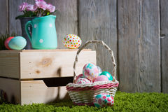 Easter eggs painted on a wooden background. Easter eggs painted on a wooden background of boards on green grass Royalty Free Stock Photo