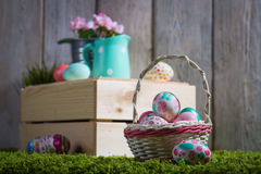 Easter eggs painted on a wooden background. Easter eggs painted on a wooden background of boards on green grass Stock Photo