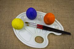 Easter eggs on a palette with brushes, there is a free place to fill stock photos