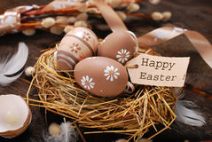 Easter eggs and paper tag with greetings in nest Stock Photography