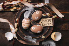 Easter eggs and paper tag with greetings in plate on rustic tabl Royalty Free Stock Images