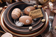 Easter eggs and paper tag with greetings in plate on rustic tabl Stock Photos