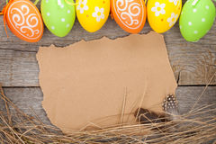 Easter eggs and paper for your greetings on wooden background Stock Images