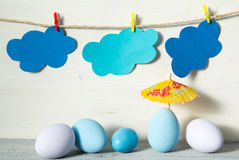 Easter eggs in pastel colors, yellow rice paper umbrella and paper clouds on a clothespins, on white wooden background Stock Photo