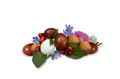 Easter eggs with pastries and flowers on a white background Stock Photos