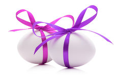 Easter eggs with pink and purple ribbons isolated on the white  Stock Images