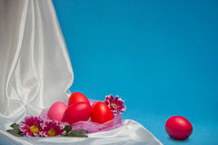 Easter eggs pink and red on white cloth on a blue background Royalty Free Stock Photos
