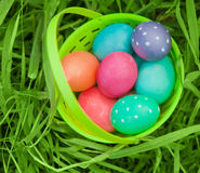 Easter eggs in plastic pail. Easter eggs in a green plastic pail sitting in the grass royalty free stock image