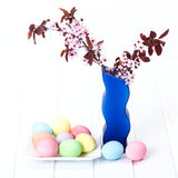 Easter eggs on plate with blooming branch Royalty Free Stock Images