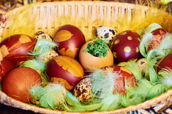 Easter eggs on the plate. Easter holidays, colorful eggs on the straw plate Royalty Free Stock Image