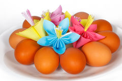 Easter eggs on the plate and a paper flowers Stock Images