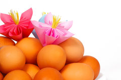 Easter eggs on the plate and a paper flowers Stock Photos