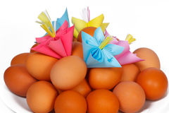 Easter eggs on the plate and a paper flowers Royalty Free Stock Photos