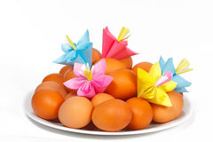 Easter eggs on the plate and a paper flowers Royalty Free Stock Image