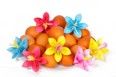 Easter eggs on the plate and a paper flowers Royalty Free Stock Photography