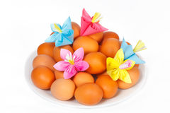 Easter eggs on the plate and a paper flowers Royalty Free Stock Images