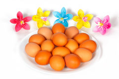 Easter eggs on the plate with a paper flowers Stock Photos