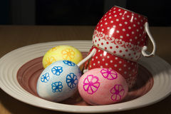 Easter eggs on a plate with two ceramic cups Royalty Free Stock Images