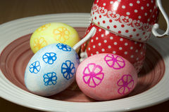 Easter eggs on a plate with two ceramic cups Stock Images