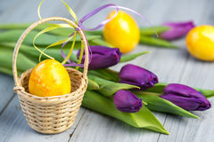 Easter eggs and purple flowers. Easter eggs in the basket and purple flowers on grey wooden background Royalty Free Stock Photos