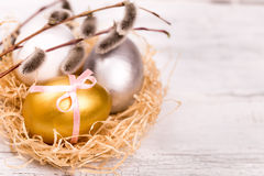 Easter eggs and pussy willow branch. On a wooden background Royalty Free Stock Photos