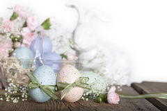 Easter Eggs with Rabbit. Two speckled Easter eggs with green ribbons tied into bows, white ceramic bunny, glass basket filled with eggs and pink carnations stock photography