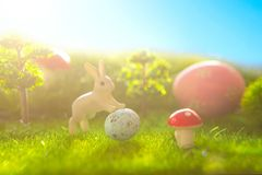 Easter eggs and rabbits. Holiday nature concept with easter hunt. Eggs in the sunny meadow. Stock Image