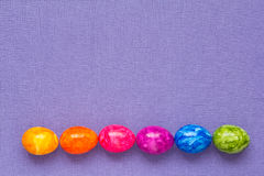Easter Eggs rainbow colours lilac. Easter Eggs in rainbow colours on lilac background with copy space Royalty Free Stock Photos