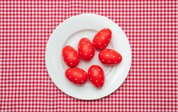 Easter eggs, red with dots, in a white plate, red checkered tablecloth background. Top view royalty free stock image