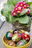 Easter eggs and red primula flowers on wooden table Stock Photography