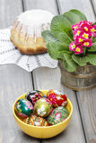 Easter eggs and red primula flowers on wooden table Royalty Free Stock Photo