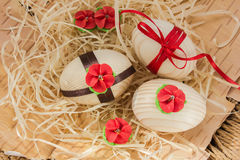 Easter eggs with ribbon and red flowers. Background birch bark and straw Stock Photo