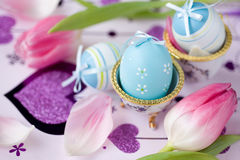 Easter eggs with ribbons and flowers. Easter eggs and pink tulips Royalty Free Stock Photos