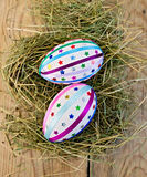 Easter eggs with ribbons and sequins on board Royalty Free Stock Images