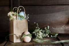 Easter Eggs with Ribbons. Speckled Easter eggs tied with green ribbons in brown paper handled bag, flowers blurred in background Stock Photos