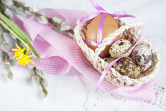 Easter eggs with ribbons in a wicker basket, next to the willow and daffodil (yellow narcissus) Stock Photo