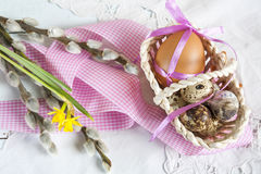 Easter eggs with ribbons in a wicker basket, next to the willow and daffodil (yellow narcissus) Stock Images