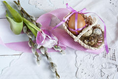 Easter eggs with ribbons in a wicker basket, next to the willow and tulip. Stock Images