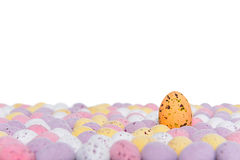 Easter eggs rising. Candy covered chocolate easter eggs with one rising above the others, space above for your own message Royalty Free Stock Images