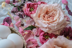 Easter eggs and roses. With other flowers on the table Royalty Free Stock Image