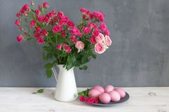 Easter eggs and roses. Pink Easter eggs in plate and spray roses in jug on shabby white wooden table against gray wall Stock Photos