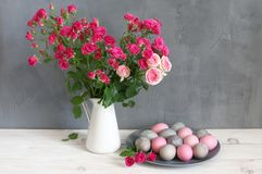 Easter eggs and roses. Pink and grey Easter eggs in plate and spray roses in jug on shabby white wooden table against gray wall Royalty Free Stock Images