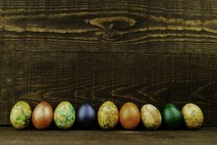 Easter eggs in a row on a dark brown wooden background, copy space stock image