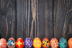 Easter eggs in a row on dark wooden background. Royalty Free Stock Photos